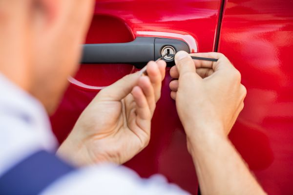 Person Opening Car Door With Lockpicker